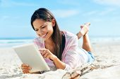 carefree woman uses touchpad tablet technology on the beach with internet vacation