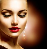 Beauty Woman with Perfect Makeup. Beautiful Professional Holiday Make-up. Red Lips Beauty Girl's Fac