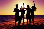 People (two couples) on the beach having a party, drinking and having a lot of fun in the sunset (on