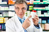 Pharmacist in pharmacy, he is holding a bottle with pharmaceuticals in his hand