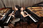 Two people, a couple playing duet musical performance with two grand pianos