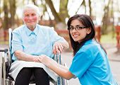 stock photo of trust  - Kind doctor nurse outdoors taking care of an ill elderly woman in wheelchair - JPG