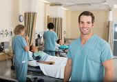 stock photo of anesthesia  - Portrait of young male nurse with colleagues examining patients in PACU - JPG
