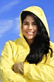 stock photo of native american ethnicity  - Portrait of beautiful smiling brunette girl wearing yellow raincoat against blue sky - JPG