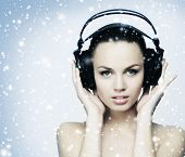 Beautiful girl listening to the music over the snowy winter background