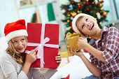 image of guess  - Portrait of happy siblings holding giftboxes and guessing what is inside on Christmas evening - JPG