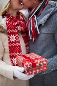 Image of amorous guy giving his girlfriend Christmas present while kissing her