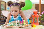 Girl in a fairy costume blew out candles on a pizza