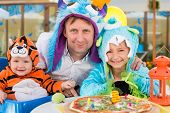 stock photo of cute tiger  - Father with daughter in monster costumes and baby boy in tiger costume celebrate the birthday in a cafe - JPG