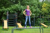 Beautiful girl standing on the parallel bars on the outdoor sports ground