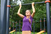 Young beautiful girl performing pull ups on the outdoor sports ground