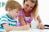 stock photo of homework  - Mother Helping Son With Homework In Kitchen - JPG