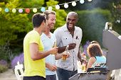 stock photo of propose  - Group Of Men Cooking On Barbeque At Home - JPG