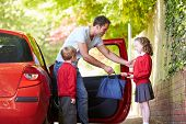 stock photo of driving school  - Father Driving To School With Children - JPG