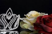 stock photo of pageant  - Rhinestone pageant tiara and roses on glass - JPG
