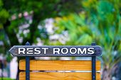 picture of braille  - Wodden restroom sign outside in a forest - JPG
