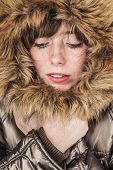 stock photo of frostbite  - Young girl wearing winter coat warming herself with fur hood up - JPG