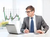 business, office and money concept - businessman in suit and black eyeglasses with laptop computer,