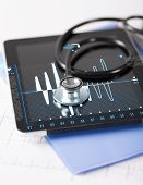 healthcare, medicine and technology concept - tablet pc, stethoscope and electrocardiogram