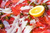 Fresh Sliced raw beef meat with lemon on the table