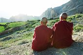 stock photo of wander  - Two Indian tibetan old monks lama in red color clothing sitting in front of mountains - JPG