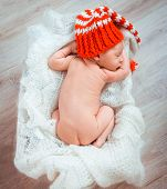 Cute newborn baby sleeps in a santa claus hat