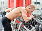 Young Man Resting On Dumbbells Rack After Workout In Gym