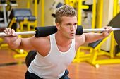 stock photo of squatting  - Handsome young man doing squats in gym with barbell - JPG