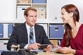 Smiling woman talking to tax consultant in his office