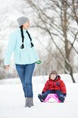 Portrait of happy mother with little child son boy on sleigh in winter outdoors