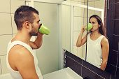 sad man drinking tea and looking at a woman in the mirror