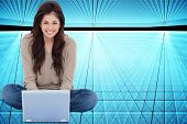 Composite image of a woman smiling as she looks forward in front of her laptop with crossed legs.