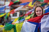 Young girl and Buddhist prayer flags flying.