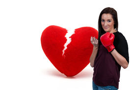 image of heartbreaking  - Beautiful woman in wearing a boxing glove in front of a broken heart  - JPG
