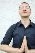 picture of namaste  - A portrait of a man in a shirt looking at the camera with a namaste greeting - JPG