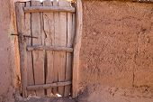 Old wooden door and adobe wall