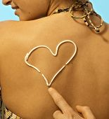 Women with sunscreen cream heart sign on back. Smiling, swimsuit. Sun, summer, close up, sunbathing.