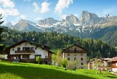 Houses are surrounded by the Dolomites, Comune di Falcade, Italy. Houses are surrounded by the Dolom