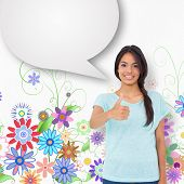 Happy brunette giving thumbs up with speech bubble against digitally generated girly floral design
