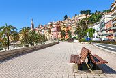 Promenade along streets and colorful houses of Menton - town and touristic resort on French Riviera.