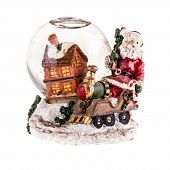 stock photo of christmas theme  - a christmas themed snow globe with a house and a santa figurine isolated over white - JPG