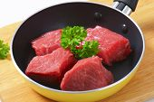 three raw pieces of beefsteak in the pan