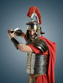 stock photo of legion  - Roman Soldier with sword ready for war isolated on a blue background - JPG