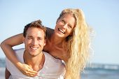 Beach couple fun - lovers on romantic travel doing piggyback in love on honeymoon vacation summer ho