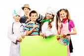 A group of children dressed in costumes of different professions holding white board. Isolated over white.
