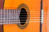 stock photo of nylons  - body of spanish acoustic guitar with six nylon strings close up - JPG