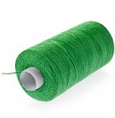 Bobbin of green  cotton thread close up isolated on white background