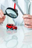 a model of a car is examined by a doctor. symbolic photo for workshop, service and car buying.