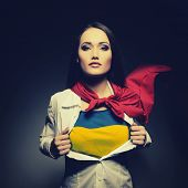 Young woman opening shirt painted in colors of ukrainian flag like superhero. Girl twenty-years-old