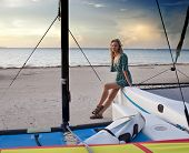 The woman on the seashore sits on board a catamaran
